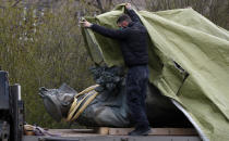 A worker covers the statue of a Soviet World War II commander Marshall Ivan Stepanovic Konev after its been removed from its site in Prague, Czech Republic, Friday, April 3, 2020. Marshall Konev led the Red Army forces that liberated Prague and large parts of Czechoslovakia from the Nazi occupation in 1945. His monument, unveiled in the Prague 6 district in 1980 when the country was occupied by Soviet troops, has been a source of controversy. (AP Photo/Petr David Josek)