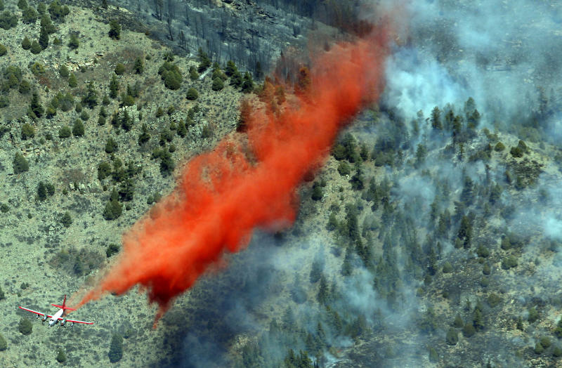 A trail of slurry is deposited by a bomber during a run over a smoldering ridge in the Lower North Fork Wildfire burning in the foothills community of Conifer, Colo., southwest of Denver on Tuesday, March 27, 2012. Firefighters are now able to actively battle the blaze on the ground that started on Monday and has already destroyed at least 16 homes in the rugged terrain. (AP Photo/David Zalubowski)