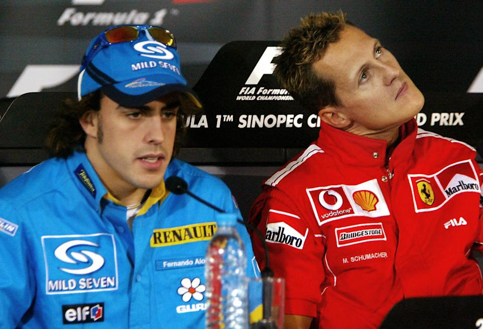 SHANGHAI, CHINA:  Spanish F1 driver Fernando Alonso (L) addresses a press conference as F1 World champion Michael Schumacher of Ferrari looks up, after the first day of the F1 China Grand Prix practice session at the Shaghai International Circuit, 24 September 2004.  China's first F1 Grand Prix will be held 26 September.  AFP PHOTO / Yoshikazu TSUNO  (Photo credit should read YOSHIKAZU TSUNO/AFP via Getty Images)