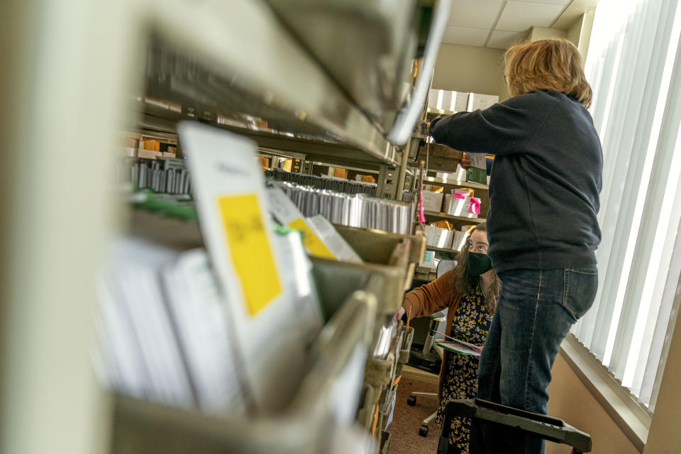 Election workers Madison Takala, left, and Mary Pluszczynsky file returned absentee ballots ahead of Tuesday's general election at the city clerk office in Warren, Mich., Wednesday, Oct. 28, 2020. (AP Photo/David Goldman)