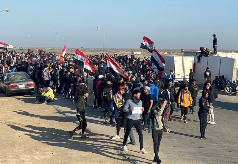 Iraqi demonstrators carry Iraqi flags as they block the road during ongoing anti-government protests in the outskirts of Nassiriya