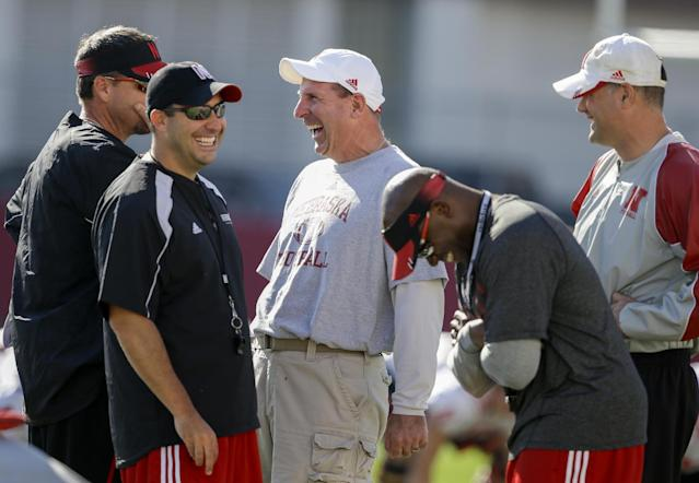 Nebraska head coach Bo Pelini, center, jokes with members of his staff, from left: wide receivers coach Rich Fisher, defensive coordinator John Papuchis, secondary coach Charlton Warren, and assistant coach Ross Els, during team practice in Lincoln, Neb., Wednesday, Aug. 13, 2014. (AP Photo/Nati Harnik)