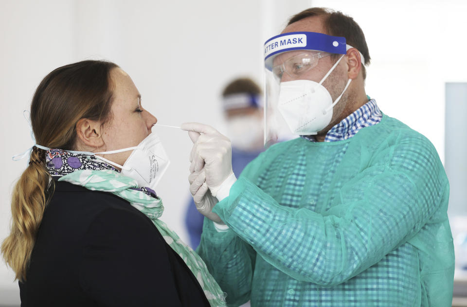 A pharmacist takes a swab from a woman's nose in an adjoining room in Hagen, Germany, Monday, March 8, 2021. The free Corona rapid tests for all citizens were initially only offered by a few pharmacies in North Rhine-Westphalia on the launch day because of many unanswered questions. ( Oliver Berg/dpa via AP)