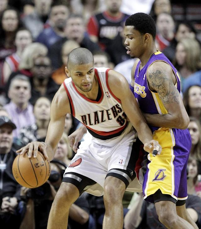 Portland Trail Blazers forward Nicolas Batum, left, of France, maneuvers against Los Angeles Lakers guard Kent Bazemore during the first half of an NBA basketball game in Portland, Ore., Monday, March 3, 2014. (AP Photo/Don Ryan)