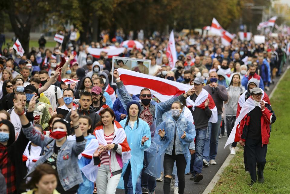 People with old Belarusian national flags march during an opposition rally to protest the official presidential election results in Minsk, Belarus, Sunday, Sept. 27, 2020.Hundreds of thousands of Belarusians have been protesting daily since the Aug. 9 presidential election. (AP Photo/TUT.by)