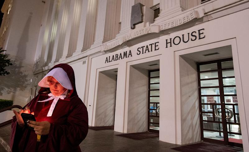 Anti abortion ban bill protestor Bianca Cameron-Schwiesow, dressed as a handmaid, waits outside of the Alabama statehouse after HB314, the near-total ban on abortion bill, passed the senate in Montgomery, Ala., on Tuesday May 14, 2019.