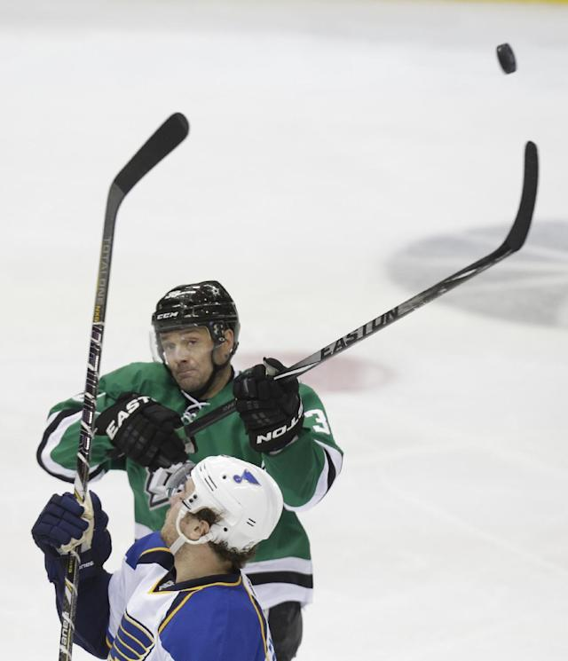Dallas Stars center Vernon Fiddler (38) reaches for the puck over St. Louis Blues defenseman Kevin Shattenkirk during the second period of an NHL hockey game Friday, April 11, 2014, in Dallas. (AP Photo/LM Otero)