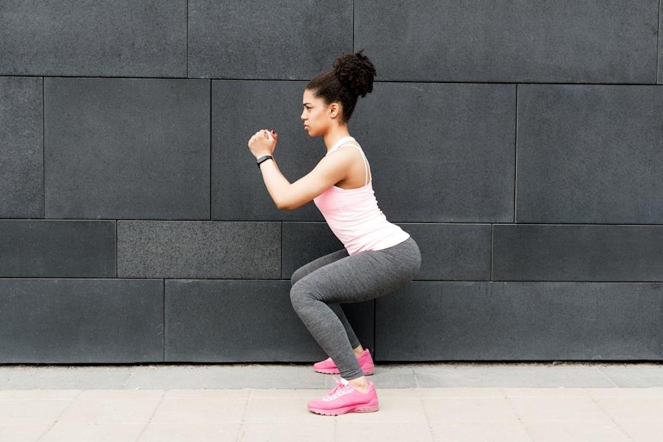 """<p>Jennings also said that """"iso squat holds are a key intro to bodyweight squats while helping to engage our quads, glutes, hamstrings, and core.""""</p> <ul> <li>Stand with your feet shoulder-width apart or slightly wider and with your chest tall. Extend your hands straight out in front of you, hold them at chest level, or place them behind your head.</li> <li>Bend at your knees and hips and press your weight back into your heels with your knees over your ankles, pushing your butt out like you're sitting onto a chair. Keep your chest lifted, and do not let your lower back round.</li> <li>Squat down as low as you can, still keeping your head and chest lifted.</li> <li>Jennings said to hold for 15 seconds before standing back up.</li> </ul>"""
