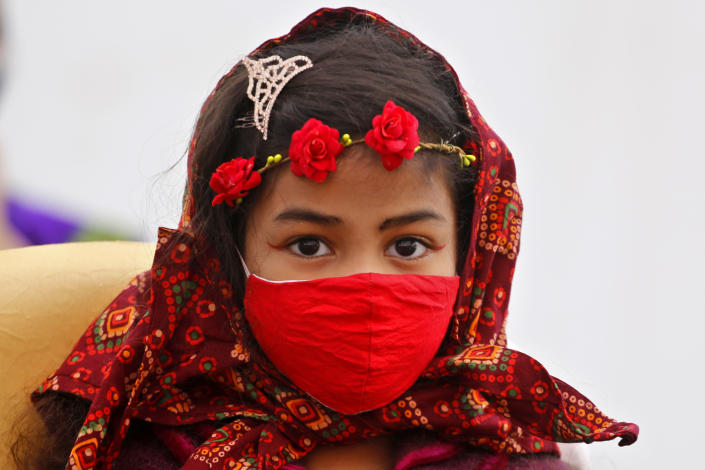 A Christian girl wearing a face mask as a precaution against the coronavirus attends the Christmas mass at a church in Ahmedabad, India, Friday, Dec. 25, 2020. (AP Photo/Ajit Solanki)