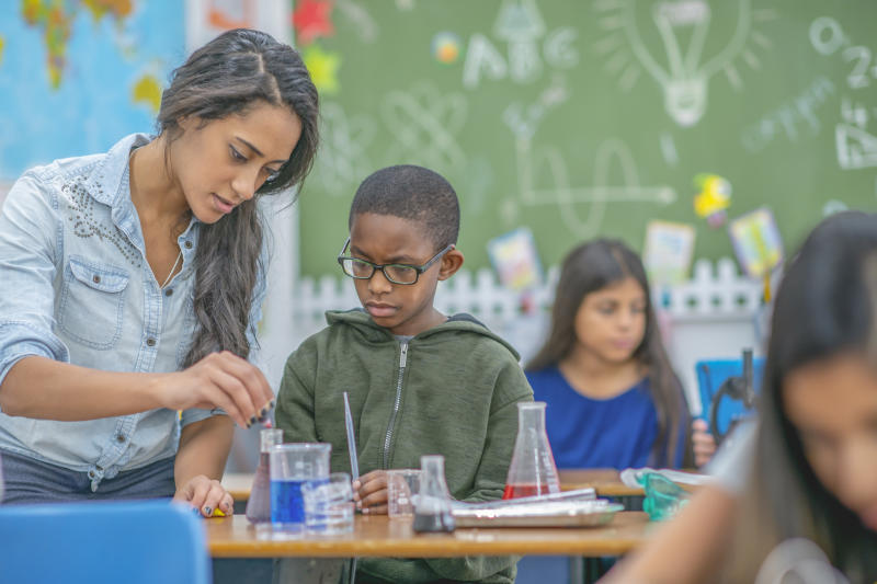 A young female teacher helps a boy in her class to conduct a chemistry experiment.