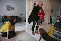 """In this Nov. 26, 2013 photo, Shirin Majid, left, watches as her husband, Will Townsend, plays with their 9-month-old daughter, Ella Townsend, at home in New York. Majid, who works for the internet startup Quirky, is home during her company's quarterly """"blackout"""" week break from work. Quirky's CEO, Ben Kaufman, makes the whole company stop working and take breaks so they don't burn out. (AP Photo/Bebeto Matthews)"""