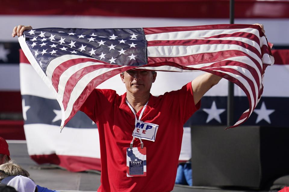 A supporter of President Donald Trump waves the American flag waiting for the arrival of Trump for a campaign rally Monday, Oct. 19, 2020, in Tucson, Ariz. (AP Photo/Ross D. Franklin)