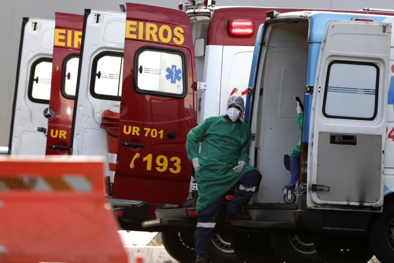 Health workers take a break near their ambulance after moving a patient suspected of being infected with COVID-19 to the HRAN Hospital, specialized in the care of new coronavirus cases, in Brasilia, Brazil, Monday, Aug. 3, 2020. (AP Photo/Eraldo Peres)