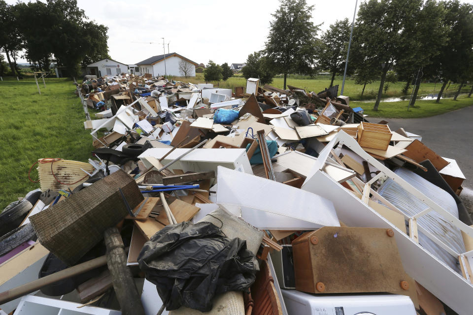 Bulky Piles of waste goods line a street after floods destroyed many homes in the village of Stotzheim, Germany, Thursday July 22, 2021. In the flood disaster area of Erftstadt-Blessem, some residents are being allowed back into their homes to clear debris after heavy rains caused devastating floods. (David Young/dpa via AP)