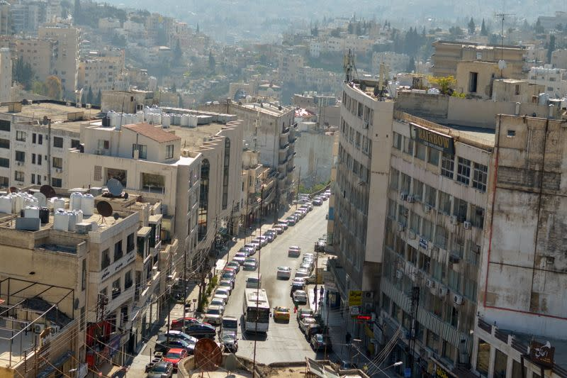 A view shows buildings as vehicles drive through a road in Amman