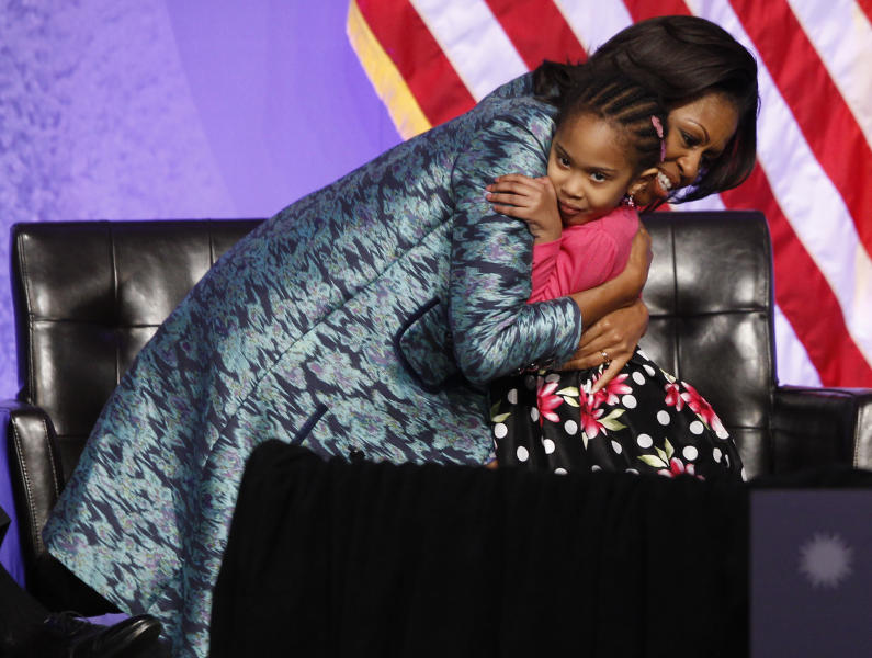Four-year-old Piper Shillingford from Stuyvesant Heights Montessori Academy in Brooklyn, N.Y., gets a hug from first lady Michelle Obama at the groundbreaking for the Smithsonian National Museum of African American History and Culture in Washington, Wednesday, Feb. 22, 2012. Students from the school had collected $600 in coins and presented it during the museum groundbreaking. (AP Photo/Charles Dharapak)