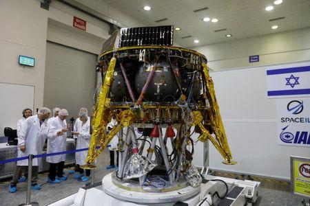 Israeli scientists stand next to an unmanned spacecraft which an Israeli team plans to launch into space at the end of the year and to land it on the Moon next year in Yahud Israel