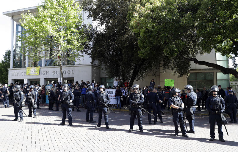 Police form a line in front of Berkeley High School as a rally for free speech takes place across the street Thursday, April 27, 2017, in Berkeley, Calif. Demonstrators gathered near the University of California, Berkeley campus amid a strong police presence and rallied to show support for free speech and condemn the views of Ann Coulter and her supporters. (AP Photo/Marcio Jose Sanchez)