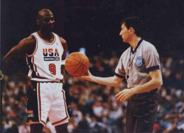 Michael Jordan posing beautiful for the camera during a game and the referee is handling him the ball