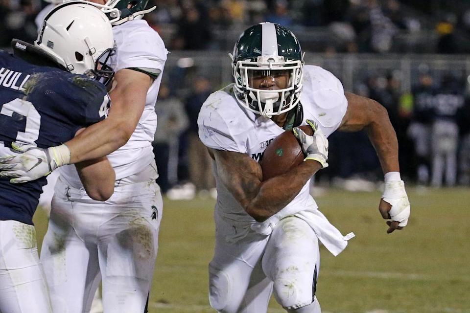 Michigan State running back Jeremy Langford (33) runs past Penn State linebacker Mike Hull (43) for a 6-yard touchdown run during the second half of an NCAA college football game in State College, Pa., Saturday, Nov. 29, 2014. Michigan State won 34-10. (AP Photo/Gene J. Puskar)