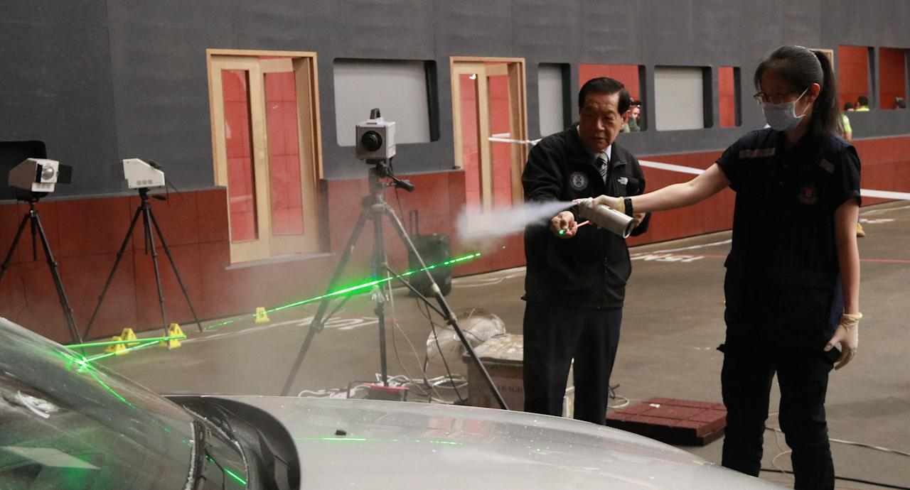 <p>Forensic scientist Dr Henry C. Lee shows one of the course participants how to detect the trajectory of a bullet using laser beams. Photo: Hannah Teoh/Yahoo News Singapore </p>