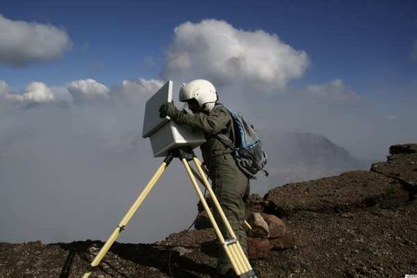 Geologist changing the data card from the time-lapse camera on the north rim of Pu'u 'O'o cone.