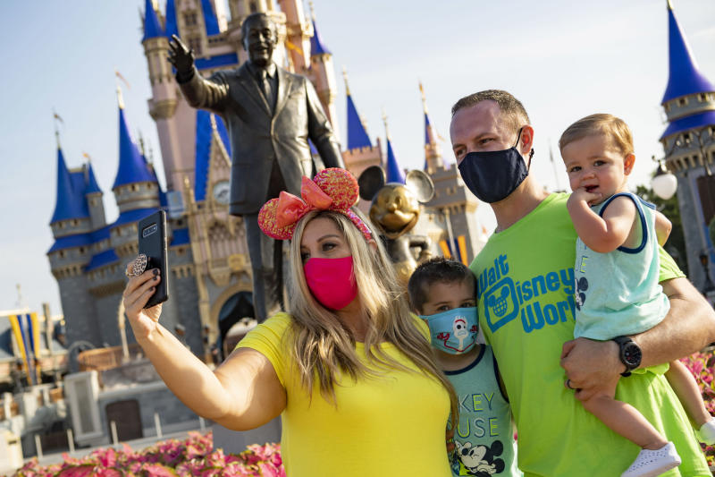 LAKE BUENA VISTA, FL - JULY 11: In this handout photo provided by Walt Disney World Resort, guests stop to take a selfie at Magic Kingdom Park at Walt Disney World Resort on July 11, 2020 in Lake Buena Vista, Florida. July 11, 2020 is the first day of the phased reopening. (Photo by Matt Stroshane/Walt Disney World Resort via Getty Images)