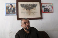 Rajab Ali Urzgani Mangol speaks during an interview to The Associated Press in Kabul, Afghanistan, Tuesday, June 1, 2021. On the wall are photos of 14-year-old Mangol as a Hazara fighter during the Afghan civili war. After the collapse of the Taliban 20 years ago, Afghanistan's ethnic Hazaras began to flourish and soon advanced in various fields, including education and sports, and moved up the ladder of success. They now fear those gains will be lost to chaos and war after the final withdrawal of American and NATO troops from Afghanistan this summer. (AP Photo/Rahmat Gul)
