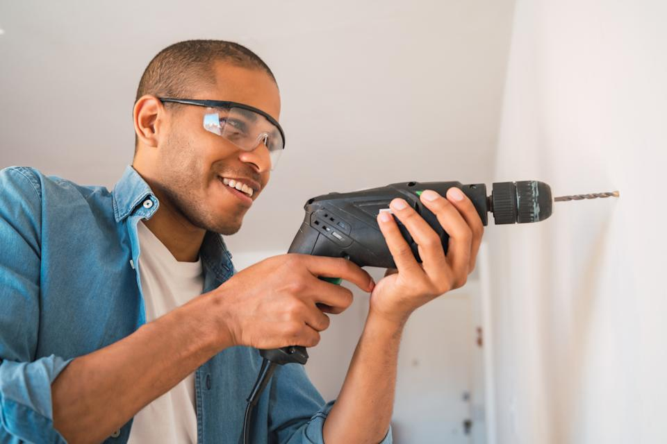 Portrait of young latin man with a electric drill and making hole in wall. Interior design and home renovation concept.