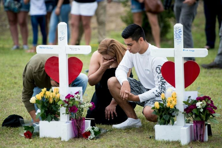 People visit a cross for Christopher Stone at a memorial for the victims of the Santa Fe High School shooting