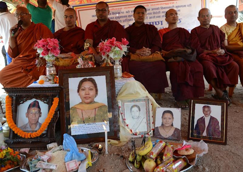 Portraits of earthquake victims are lined up as Buddhist monks offer prayers near Durbar Square, to mark the first anniversary of the 2015 Nepal earthquake, in Kathmandu, on April 24