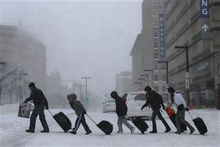 Travelers leave the Back Bay train and subway station during a winter nor'easter snow storm in Boston, Massachusetts January 3, 2014. REUTERS/Brian Snyder