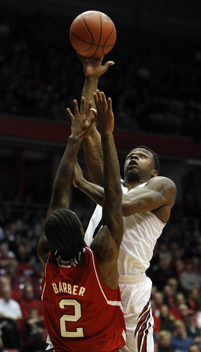 Cincinnati guard Ge'Lawn Guyn, right, goes up for a shot against North Carolina State guard Anthony Barber (2) during the first half of an NCAA college basketball game Tuesday, Nov. 12, 2013, in Cincinnati. (AP Photo/David Kohl)