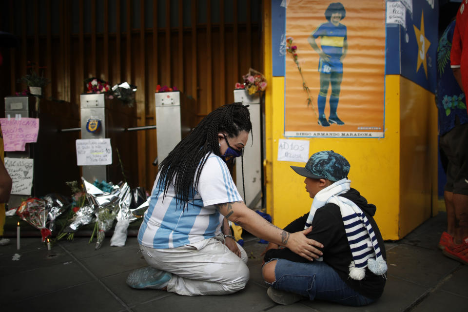 Fans mourn under a poster of Diego Maradona at the entrance of the Boca Juniors stadium, known as La Bombomera, in Buenos Aires, Argentina, Wednesday, Nov. 25, 2020. The Argentine soccer great who was among the best players ever and who led his country to the 1986 World Cup title before later struggling with cocaine use and obesity, died from a heart attack on Wednesday at his home in Buenos Aires. He was 60. (AP Photo/Natacha Pisarenko)