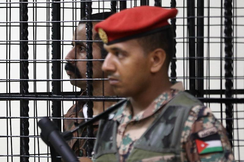 Maarik Al-Tawaiha stands behind bars during his trial at a court in Amman on July 17, 2017