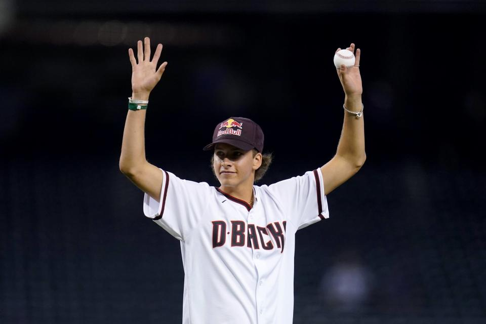 Jagger Eaton, the United States Olympic bronze medalist for men's street competition in skateboarding in the 2021 Tokyo Olympics, waves to cheering fans prior to throwing out the first pitch in a baseball game between Arizona Diamondbacks and the San Francisco Giants, Tuesday, Aug. 3, 2021, in Phoenix. (AP Photo/Ross D. Franklin)