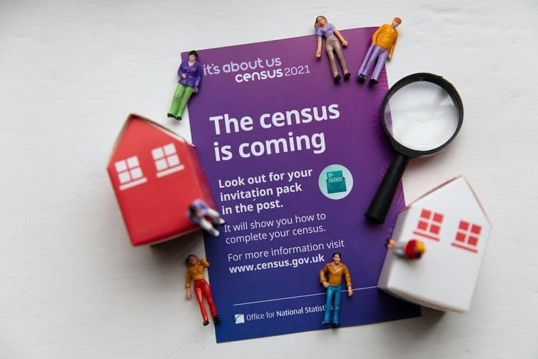 A census 2021 form currounded by models of people, houses, and a magnifying glass
