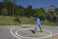 A bowler sends down a delivery during a game of cricket played by migrants in Tuzla, Bosnia, Friday, May 21, 2021. The Rome-based Baobab Experience group brought cricket equipment for the migrants in the Bosnian capital of Sarajevo and the central town of Tuzla, offering a rare opportunity for relaxation and fun for the people who spend months, if not years, stuck in camps while fleeing war and poverty in their nations and chasing their dreams of a better future. (AP Photo/Kemal Softic)