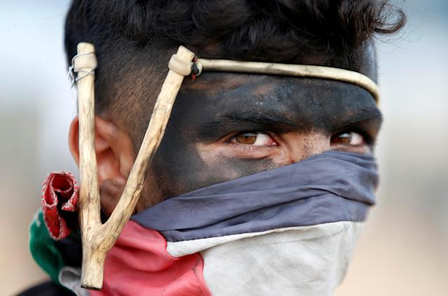 <p>A Palestinian demonstrator with a slingshot takes part in a protest against the U.S. Embassy's move to Jerusalem, at the Israel-Gaza border east of Gaza City, May 14, 2018. (Photo: Mohammed Salem/Reuters) </p>