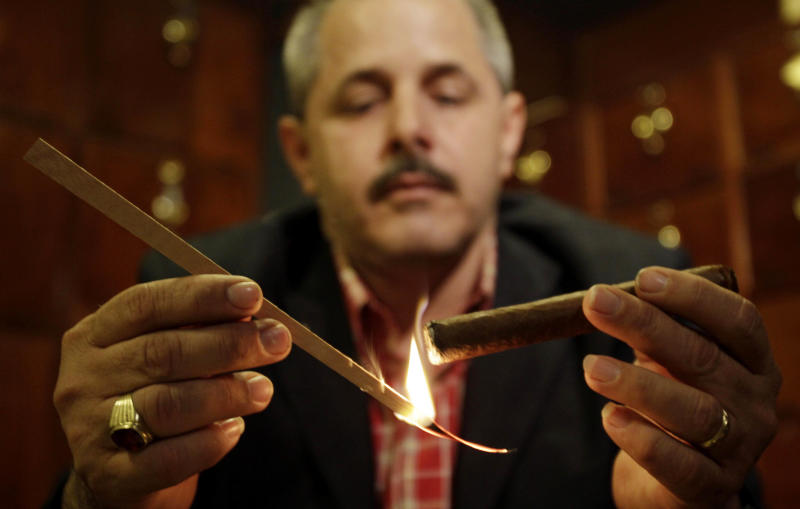 In this March 15, 2012 photo, Reinaldo Ruiz lights up his cigar at the Conde de Villanueva hotel, home to one of the city's most popular cigar rooms, in Havana, Cuba.  A number of state-owned restaurants in Havana's picturesque colonial quarter have quietly gone smoke-free in recent weeks as authorities finally implement a 2005 measure that has been almost universally flouted until now. (AP Photo/Franklin Reyes)