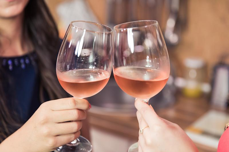 Close up of women toasting with rose wine while celebrating success.