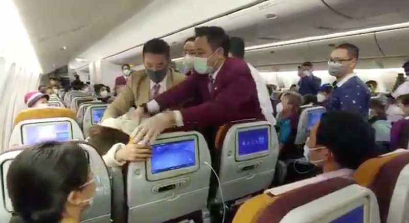 Thai Airways staff restrain a passenger.