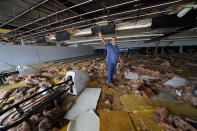 In the aftermath of Hurricane Ida, Dewayne Pellegrin a bowling alley mechanic, cleans up the heavily damaged Bowl South of Louisiana Tuesday, Aug. 31, 2021, in Houma, La. (AP Photo/David J. Phillip)