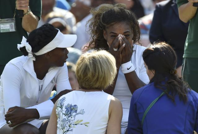 Serena Williams of the U.S. (C) appears unwell before her women's doubles tennis match with Venus Williams of the U.S. (L) against Kristina Barrois of Germany and Stefanie Voegele of Switzerland at the Wimbledon Tennis Championships, in London July 1, 2014. REUTERS/Toby Melville (BRITAIN - Tags: SPORT TENNIS TPX IMAGES OF THE DAY)