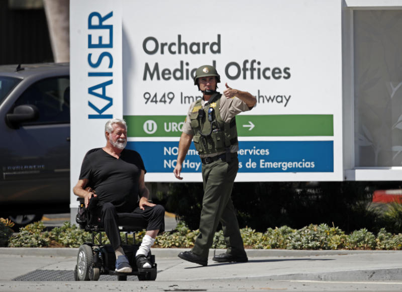 A man in a motorized wheelchair and a Los Angeles County Sheriff's deputy wait outside after staff and patients were evacuated from Kaiser Permanente Downey Medical Center, following reports of someone with a weapon at the facility in Downey, Calif., Tuesday, Sept. 11, 2018. Los Angeles County sheriff's officials say a suspect is in custody and deputies and police officers are methodically searching the complex. (AP Photo/Jae C. Hong)