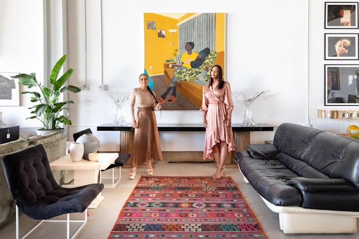"""Tricia Benitez Beanum and Sarah Mantilla Griffin pose in front of work by some of the artists in the UNREPD roster. Center: Corey Pemberton, """"Hold me down, I'll hold you up"""" 2021. Right: Bryce Batts, """"Motown,"""" """"Black Silence,"""" and """"Quarter Life Crisis,"""" top to bottom. Left: Edwin Marcelin, untitled."""