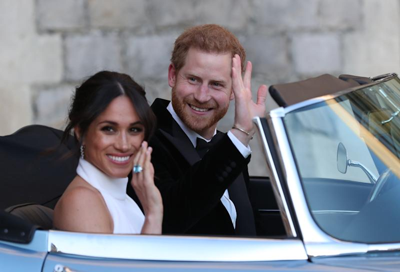 Meghan Markle and Prince Harry waving as they leave Windsor Castle after their wedding to attend an evening reception at Frogmore House, hosted by the Prince of Wales on May 19, 2018, in Windsor, England.