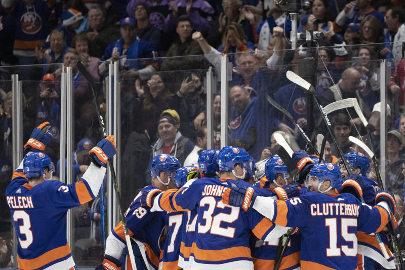 New York Islanders celebrate their 3-2 overtime win against Buffalo Sabres, Saturday, Dec. 14, 2019 in Uniondale, N.Y. (AP Photo/Mark Lennihan)