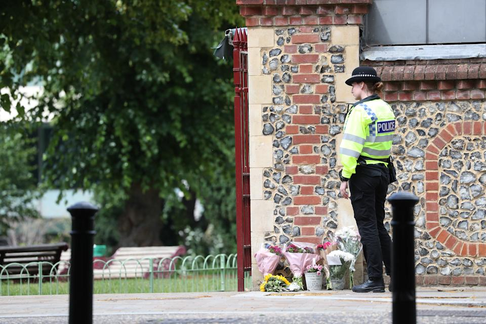 Police move flowers from Abbey Gate closer to the entrance at Forbury Gardens in Reading town centre at the scene of a multiple stabbing attack which took place at around 7pm on Saturday leaving three people dead and another three seriously injured.
