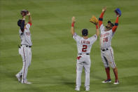 Washington Nationals' Juan Soto, left, celebrates with teammates Adam Eaton, center, and Victor Robles, right, after a baseball game against the New York Mets Tuesday, Aug. 11, 2020, in New York. The Nationals won 2-1. (AP Photo/Frank Franklin II)